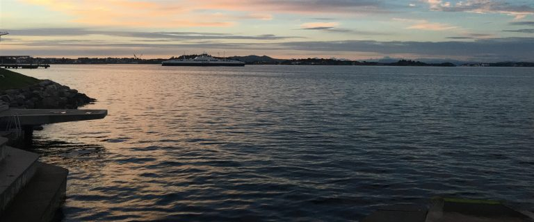A photo of the coast of Stavanger with a ferry in background. The sun is setting.