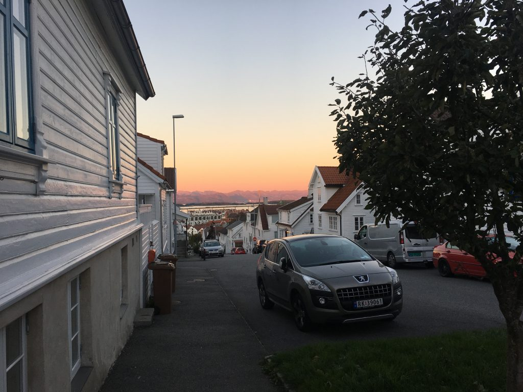 A street in Stavanger, Norway. The sun is setting in the background.