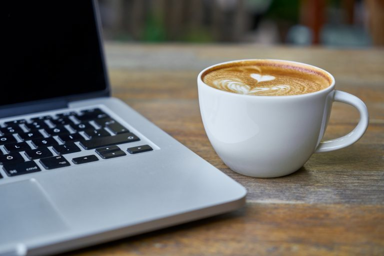 a latte and a laptop sitting on a table
